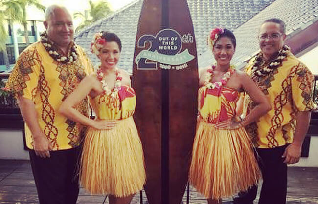 hula dancers in front of surf board