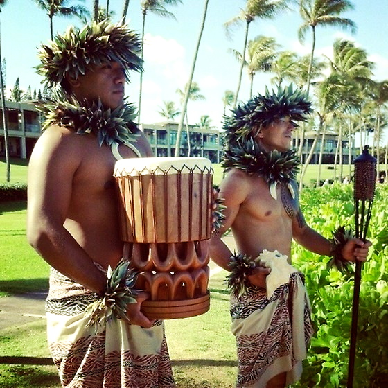 hula entertainers holding hawaiian drum and tiki torch